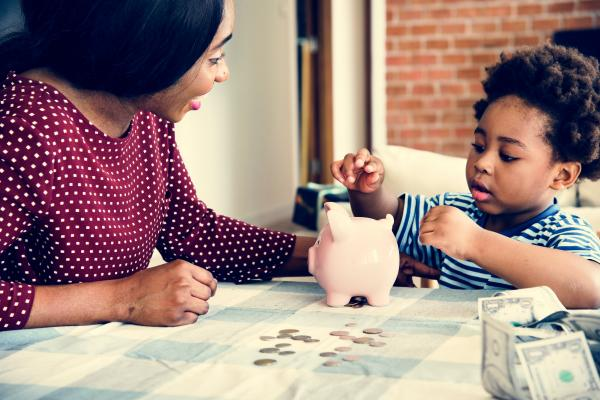 Mother and child putting money in a piggy bank