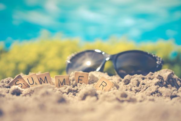 sunglasses in sand with Scrabble letters spelling summer
